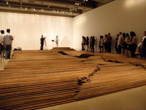 """Volunteers line up to read the names of the children who died in the 2008 Sichuan Earthquake in the Toronto Arts Gallery of Ontario's """"Read Their Names, Remember"""" performance on Aug. 18. In the foreground is one of Ai weiwei's art work, """"Straight"""", made up fo 38 tons of steel wires taken from actual buildings that collapsed in the earthquake. (Photos by Bob San)"""