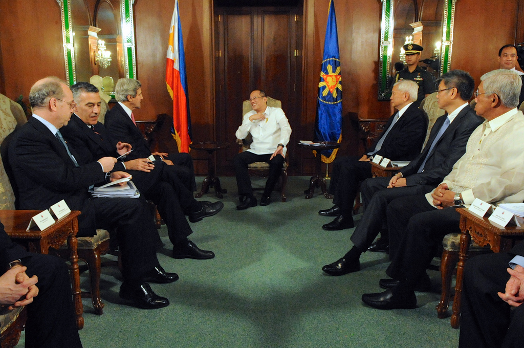 U.S. Secretary of State John Kerry and President Begnino Aquino of the Philippines sit with their respective delegations before a bilateral meeting and dinner at Malacanang Palace in Manila on December 17, 2013. [State Department photo/ Public Domain]