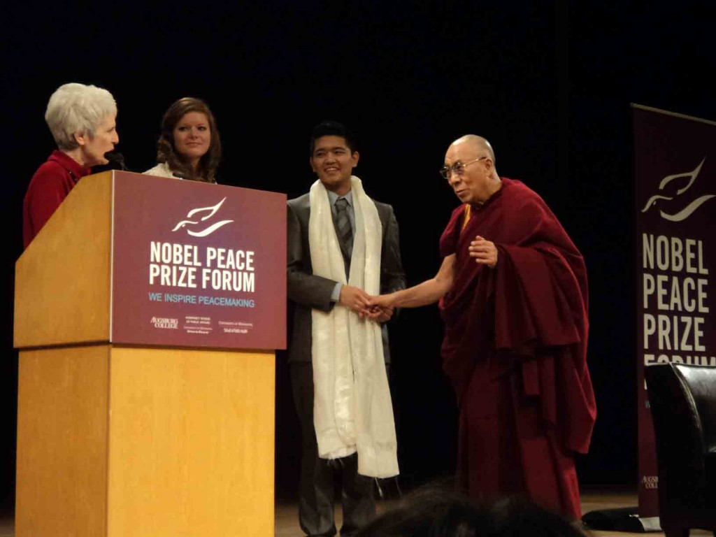 At Augsburg College last Friday, from left, His Holiness the 14th Dalai Lama holds the hand of Augsburg College student Tenzin Yeshi Paichang, the Anastasia Young of Concordia College, Moorhead, and Dr. Maureen Reed, executive director of the Nobel Peace Prize Forum at Augsburg College. (Photo by Fayrus Duale)