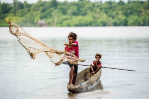 An Asmat boy throwing a net into a river. This is one of seven images of Asmat life taken by Joshua Irwandi, of Indonesia, that are part of the St. Thomas exhibition.