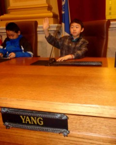 Hmong youth try the chairs of the Minneapolis City Council Chamber out for size. (Photos by Jay Clark)