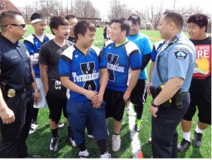 Minneapolis Police officers Blake Moua, and Kou Vang, talk strategy with the Termination X flag football team.