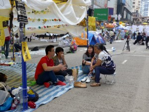 Students at the Causeway Bay protest camp answer questions from a lady in the neighborhood.