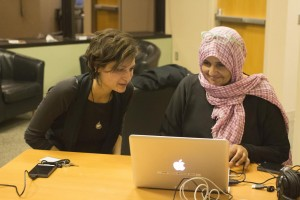 SPNN staff member Nadia Honary helps Doc U participant Aida Al-Kadi edit her film.
